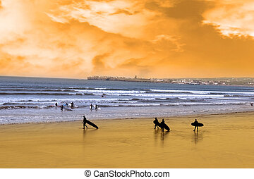 young surfers walking on sunset beach - surfers walking on...