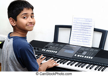 music - An handsome Indian boy learning music with an...