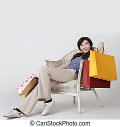 Shopping woman of Asian sit on chair and holding bags with...