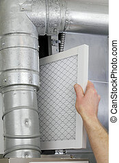 Replace Home Air Filter - A mans arm and hand seen replacing...