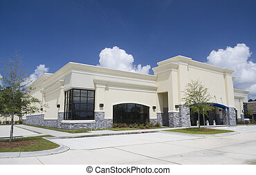 beige stucco with gray brick retail store - upscale empty...
