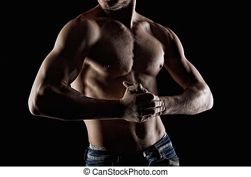 Muscular naked man on black. Focus and hands