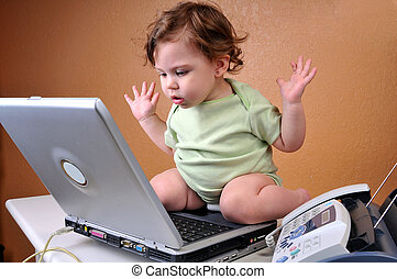 Baby looking at laptop baffled - Baby sitting on top of...