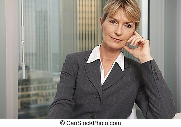 Business woman - Portrait of a senior executive by a window...