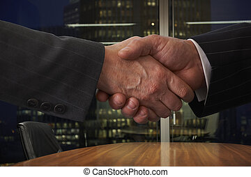 shaking hands over boardroom table with city lights in...