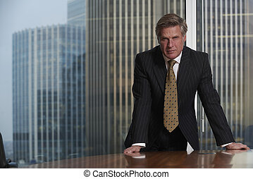 Business Man - Business man leaning on table in boardroom...