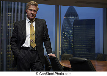 Business Man - Business man leaning on chair in boardroom...