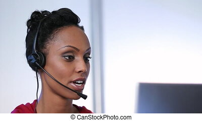 Call center - Young woman with headset talks to a customer...