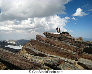 Two people at the top of high red rocky mountain, with...