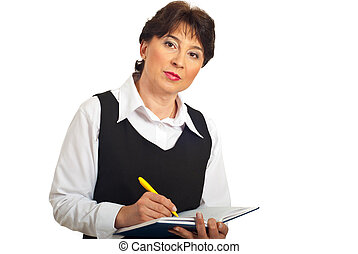 Serious manager woman taking notes in personal agenda...