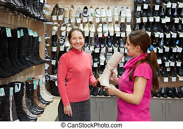 women shopping at shoe shop - Two women shopping at fashion...