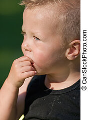 caucasian boy with finger in mouth