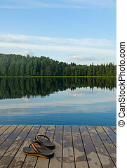 pair of slippers on a pier of the lake