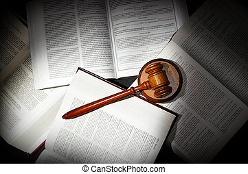 assorted open law books with legal gavel, in dramatic light