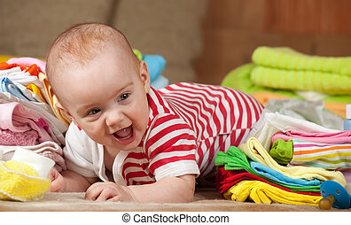 baby girl with children's wear - baby girl with heap of...