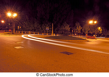 roundabout at night illuminated by streetlights and the...
