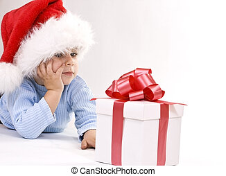 baby in santa hat - A baby wearing a Santa hat looking at a...