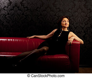 Beauty mature woman sit on red sofa