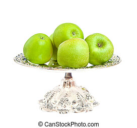 Green apples on a silver platter.