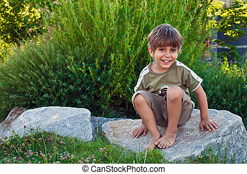 Portrait of a young boy, sitting on a rock.