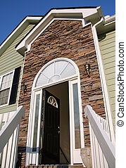 Open front door of a home with a stone facade.