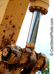 Close-up of a hydraulic piston on a back hoe.