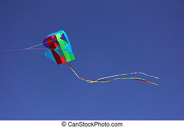 Colorful parafoil kite in flight with a blue sky background