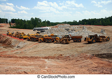 Heavy earth moving construction vehicles lined up in a row