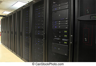 Several racks of 1u and 2u servers in black cabinets in a...