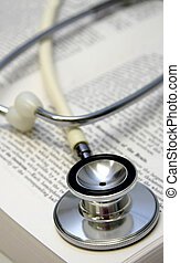 White stethoscope on a medical book. Shallow depth of field....