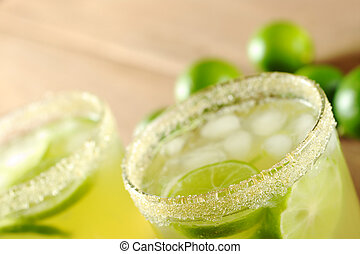 Fresh lemonade of green limes in sugar-rimmed glasses on wooden board with limes in the background (Selective Focus, Focus on the front rim of the first glass)