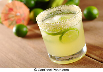 Fresh lemonade of green limes in sugar-rimmed glass on wooden board with limes and an orange paper sunshade in the background (Selective Focus, Focus on the front of the rim of the glass)