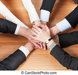 Workers hold hands together - Office workers hold hands...