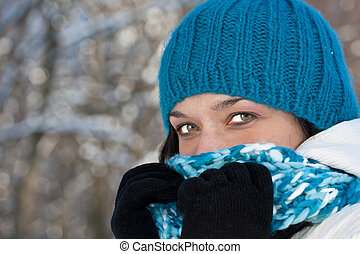 Cold winter woman covering her face in winter forest.