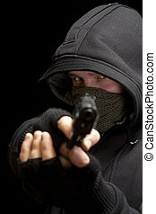 Thief with gun aiming into a camera - isolated on black...