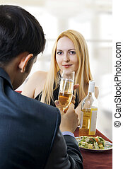 couple at restaurant dining and toasting.