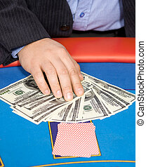 Hand with cards, and $ banknotes on table
