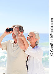 Senior couple bird watching at the beach