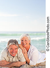 Elderly couple lying down on the beach