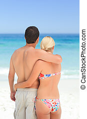 Woman huging her husband on the beach