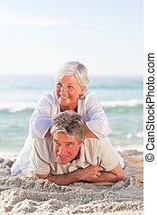 Senior couple lying down on the beach