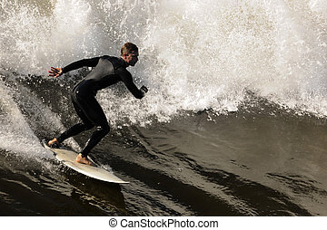 Surfer gets up on a wave. The wave twists with foam and...