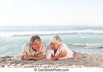 Mature couple lying down on the beach
