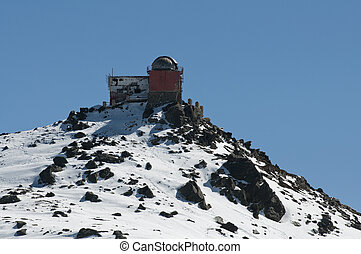 old astronomical observatory on top of a snowy mountain