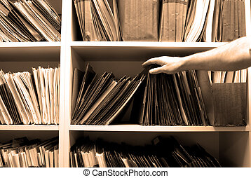 Working on Files in a File Room - Man reaching for files on...