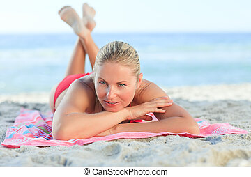 Beautiful woman lying down on the beach