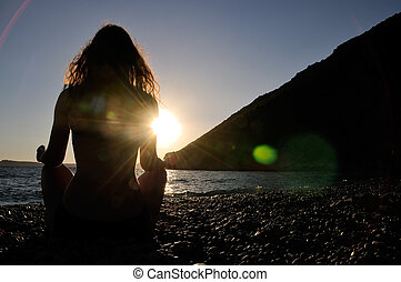 Meditation on the beach in time of sunset with lens flare
