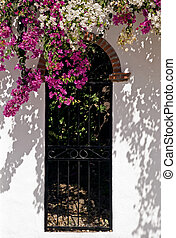 Wrought iron gate with flowers - Iron gate partially covered...