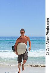 Man running on the beach with his surfboard