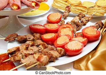 Meat canap?s and tomatoes on a plate